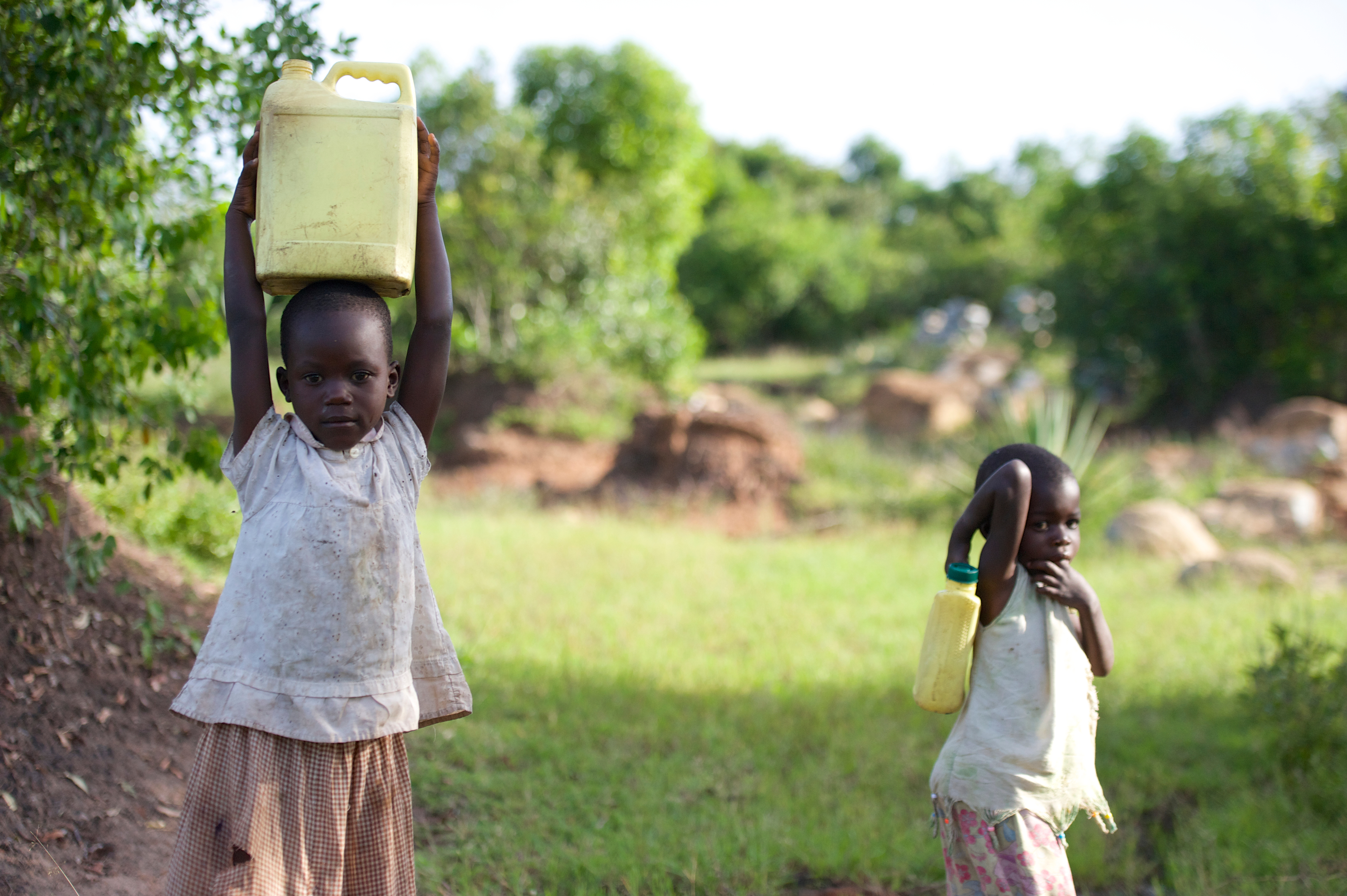 Kenyan girls carrying water on their heads